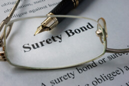 surety bond document along with glasses and a pen
