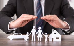 man covering paper family, car, and home with his hands
