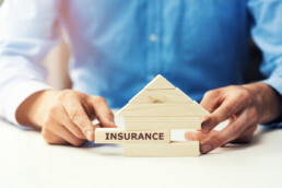 wooden block building with insurance written on one piece